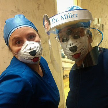 Dr. Miller and surgical assistant Lisa posing with dog facial masks
